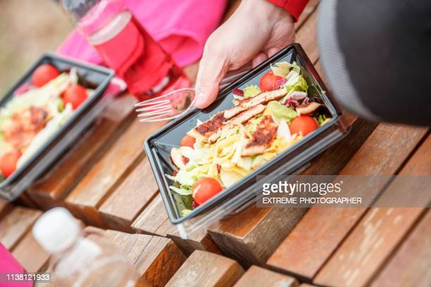 a close-up of a protein salad package containing cherry tomato, grilled chicken and various other healthy ingredients - plastic plate stock photos and pictures