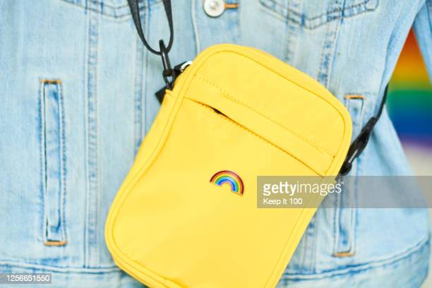 close-up of a rainbow badge on a yellow bag - pride stock pictures, royalty-free photos & images