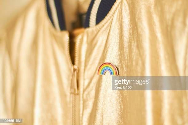 close-up of a rainbow badge on metallic gold jacket - social justice concept stock pictures, royalty-free photos & images
