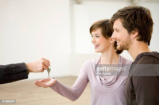 Close-up of a real estate agent's hand handing over the keys to a couple