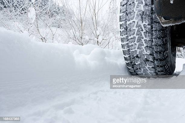 Close-up of a rear black tire in the snow creating tracks