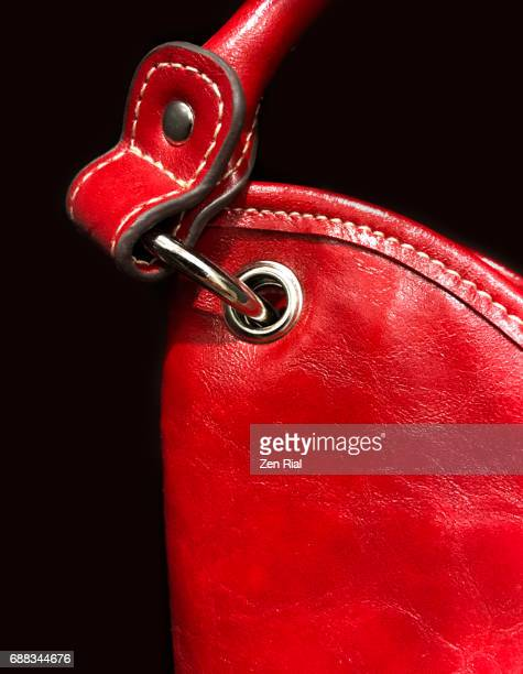 close-up of a red handbag's metal accessories on black background - leather purse stock pictures, royalty-free photos & images