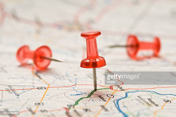 close-up of a red pushpin stuck into a map - geographical locations stock pictures, royalty-free photos & images