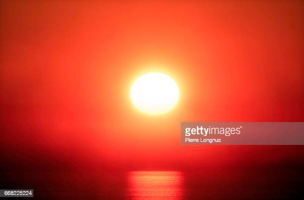 close-up of a red sunset in a the fog above the pacific ocean - heat haze stock pictures, royalty-free photos & images