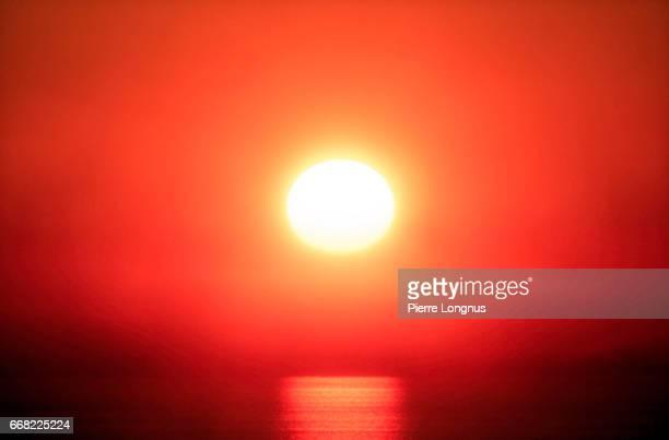 close-up of a red sunset in a the fog above the pacific ocean - bruma de calor fotografías e imágenes de stock