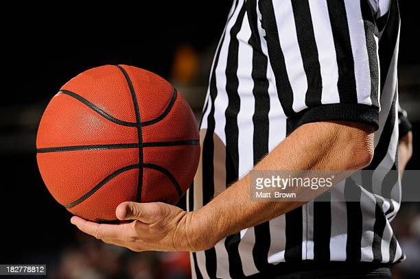 A close-up of a referee holding a standard basketball