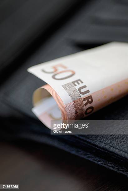close-up of a rolled up fifty euro banknote on a wallet - billet de 50 euros photos et images de collection