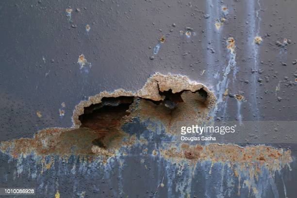 close-up of a rust hole from corrosion - rust colored stock pictures, royalty-free photos & images