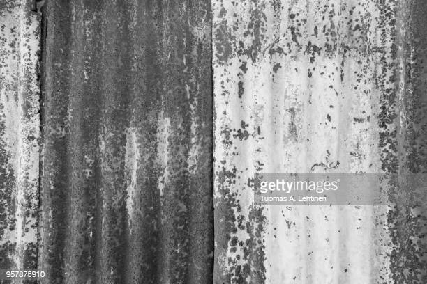 close-up of a rusty and corrugated iron metal construction site wall texture background in black and white - color manipulation stock pictures, royalty-free photos & images