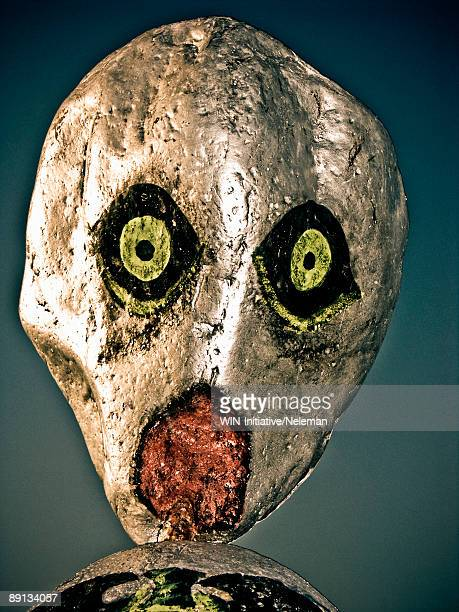 Close-up of a scarecrow face painted on a stone