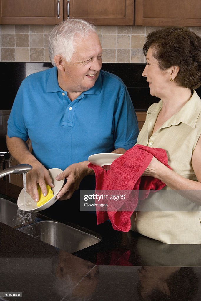 Close-up of a senior couple cleaning plates in the kitchen : Foto de stock