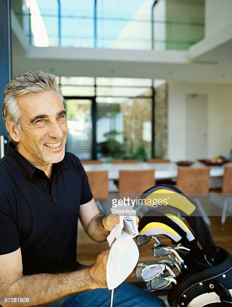 close-up of a senior man cleaning a golf club - golf club stock pictures, royalty-free photos & images
