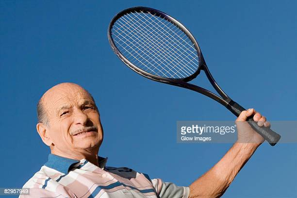 Close-up of a senior man holding a tennis racket