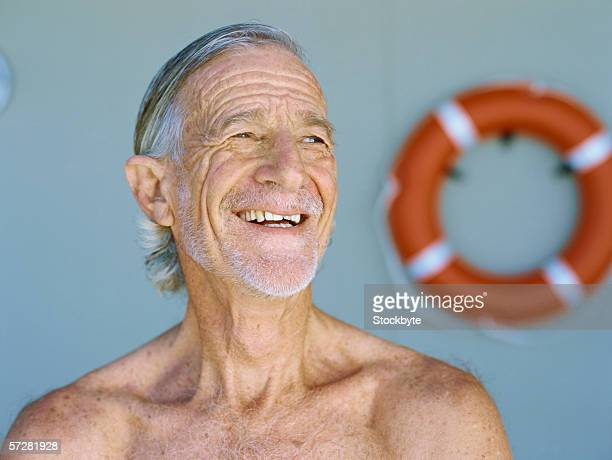 close-up of a senior man looking away bare-chested and smiling - barechested bare chested ストックフォトと画像
