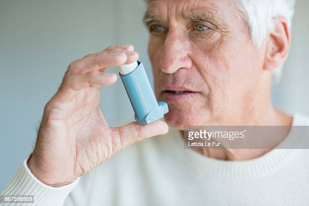Close-up of a senior man using inhaler