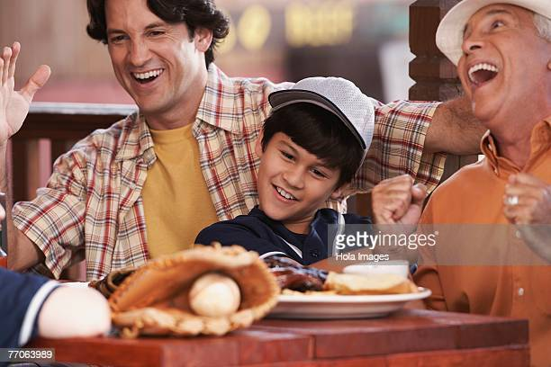 Close-up of a senior man with his son and grandson sitting in a restaurant and laughing