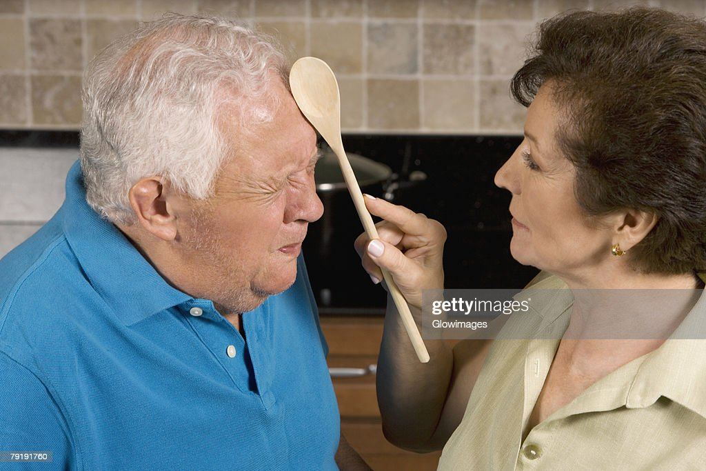 Close-up of a senior woman hitting a senior man with a ladle : Foto de stock