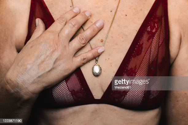 close-up of a senior woman wearing a bra and a necklace - busen nahaufnahme stock-fotos und bilder