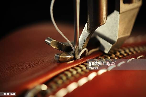 Close-up of a sewing machine with needle on red leather