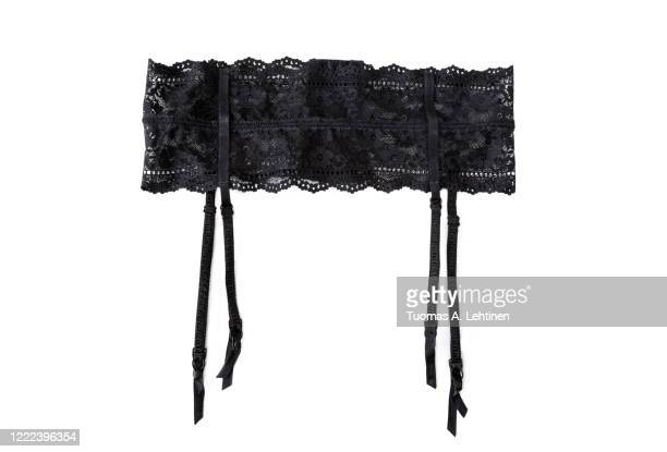 close-up of a sexy black lacy garter or suspender belt, isolated on white background. - black belt fashion item stock pictures, royalty-free photos & images