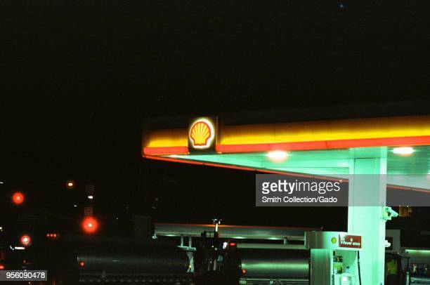 Closeup of a Shell gas station with sign and logo visible at night with gasoline trucks parked near fuel pumps Dublin California March 5 2018
