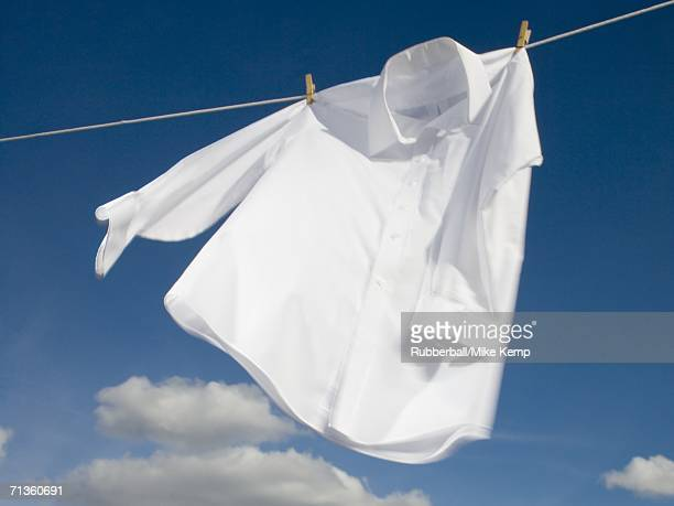 close-up of a shirt hanging on a clothesline - weißes hemd stock-fotos und bilder