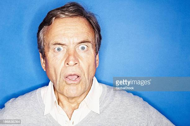 Closeup of a shocked senior man isolated against blue