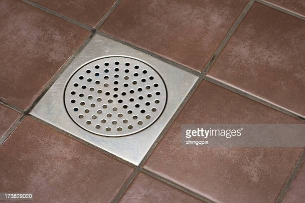 Close-up of a shower drain surrounded by brown tiles