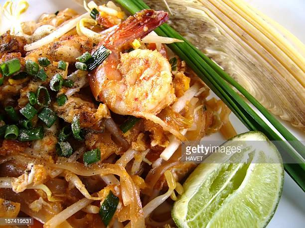 Close-up of a shrimp pad thai dish served with lime