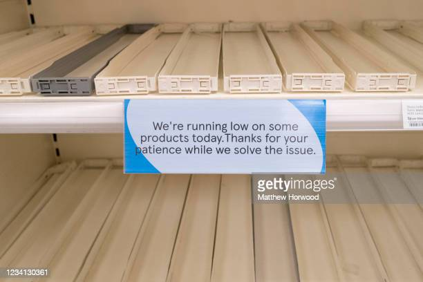 Close-up of a sign attached to an empty shelf in a Tesco store explaining that they are running low on stock on certain items on July 23, 2021 in...