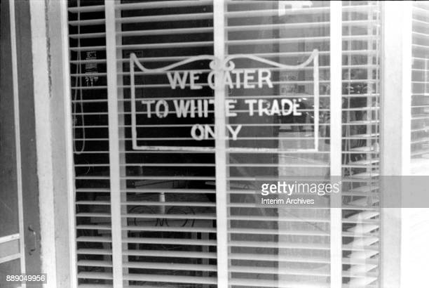 Close-up of a sign on a restaurant window that reads 'We Cater to White Trade Only,' Lancaster, Ohio, 1938.
