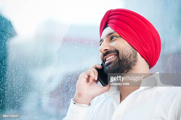 Close-up of a Sikh man talking on a mobile phone