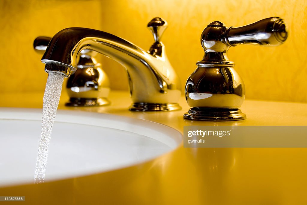 A Closeup Of A Silver Faucet Sink In A Yellow Bathroom Stock Photo ...