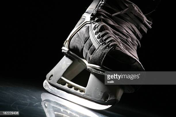 Close-up of a skate with sharp blade over shiny ice