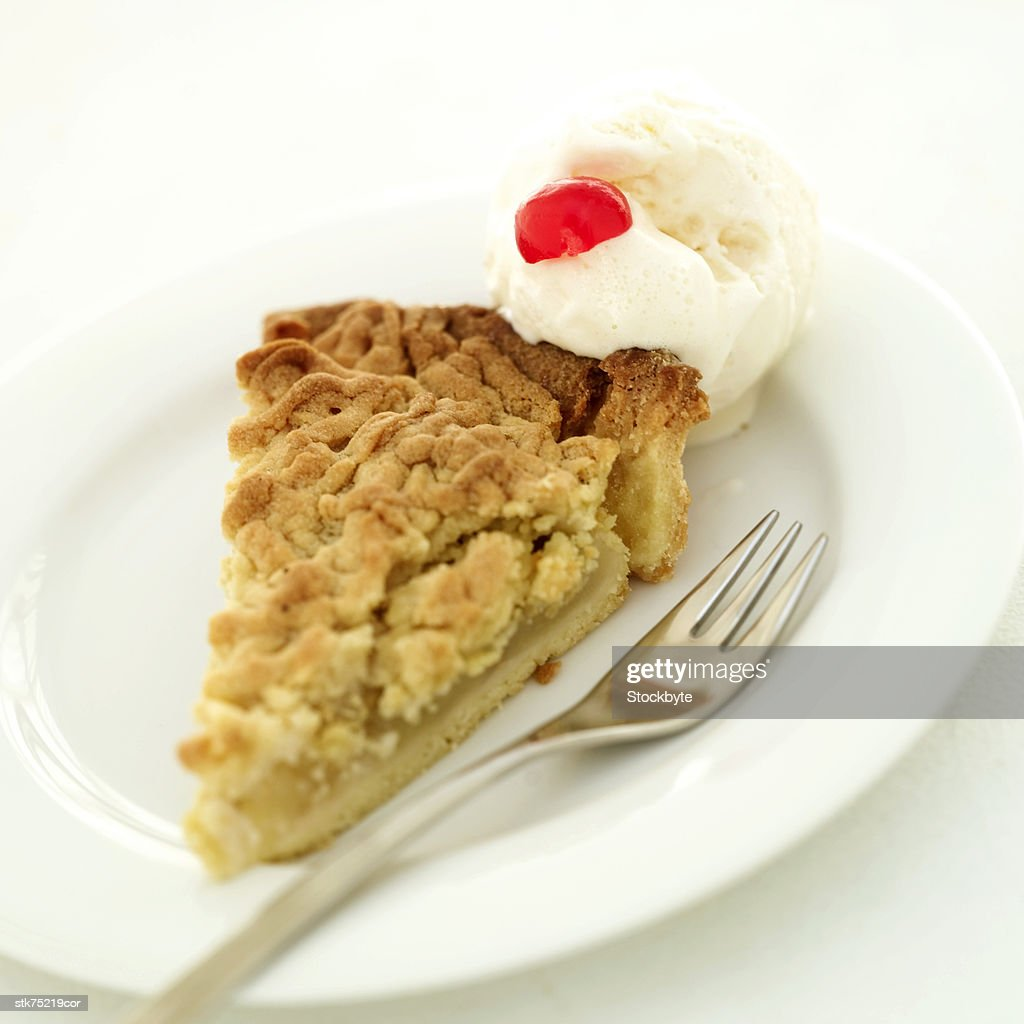 closeup of a slice of pie with ice cream and a cherry garnish