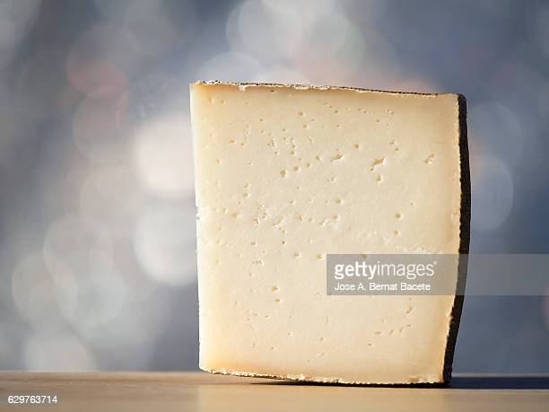 close-up of a slice of semi-cured cheese mixture, illuminated by sunlight - zwitserse kaas stockfoto's en -beelden