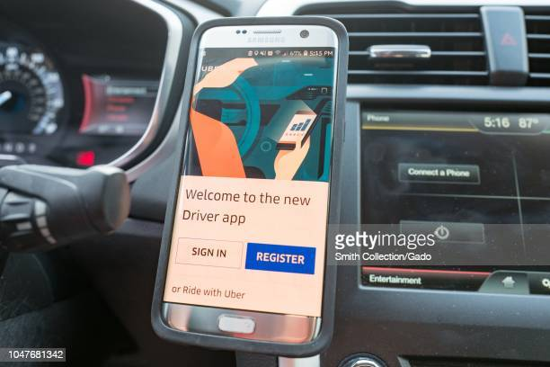 Closeup of a smartphone displaying the Uber driver app installed on a magnetic dash mount in the interior of an Uber vehicle in San Ramon California...