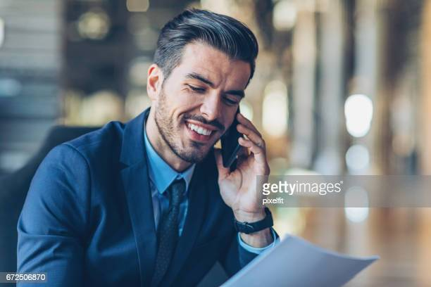 Close-up of a smiling businessman with smart phone