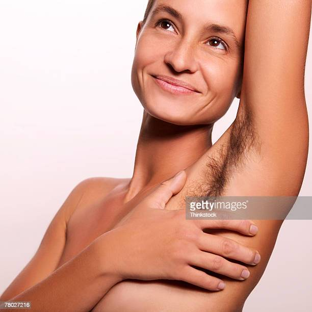 close-up of a smiling nude woman covering her breast with her hand; her armpit unshaven. - armpit hair woman stock pictures, royalty-free photos & images