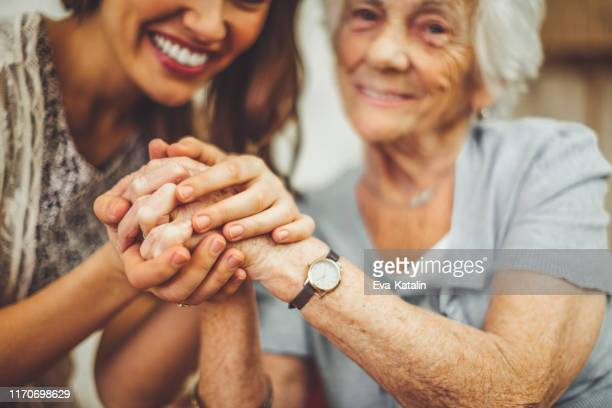 close-up of a smiling nurse holding a senior woman's hand - ricordi foto e immagini stock