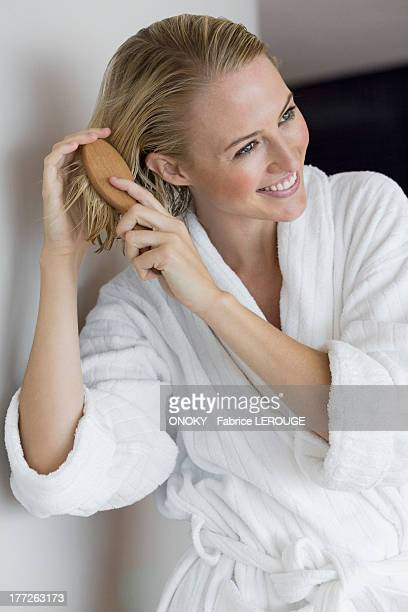 Close-up of a smiling woman brushing her hair