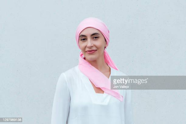 close-up of a smiling woman wearing a pink scarf in reference to cancer. - seno foto e immagini stock