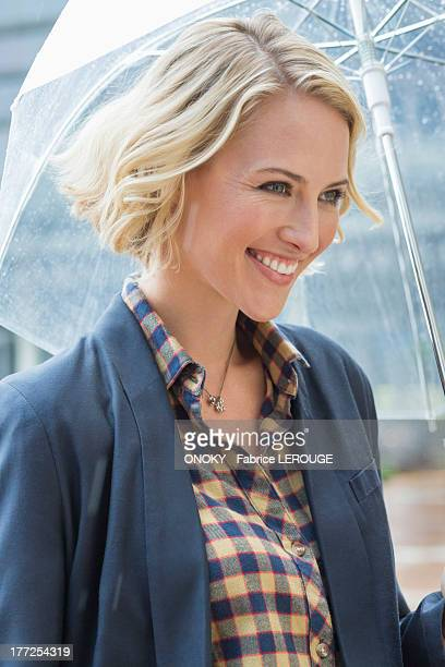 close-up of a smiling woman with an umbrella - onoky stock-fotos und bilder