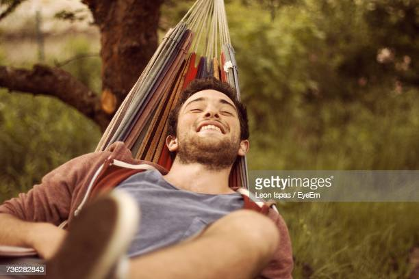 close-up of a smiling young man in hammock outdoors - hammock stock photos and pictures