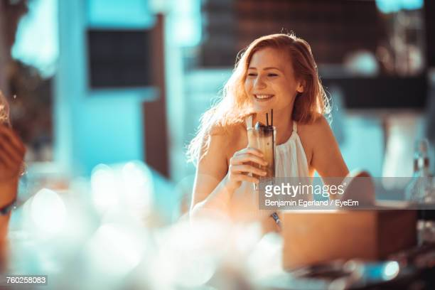 Close-Up Of A Smiling Young Woman Drinking Drink