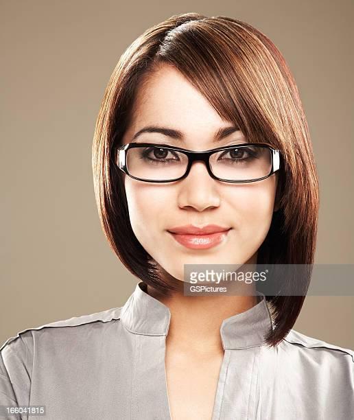 Gros plan d'une jeune femme à lunettes souriant
