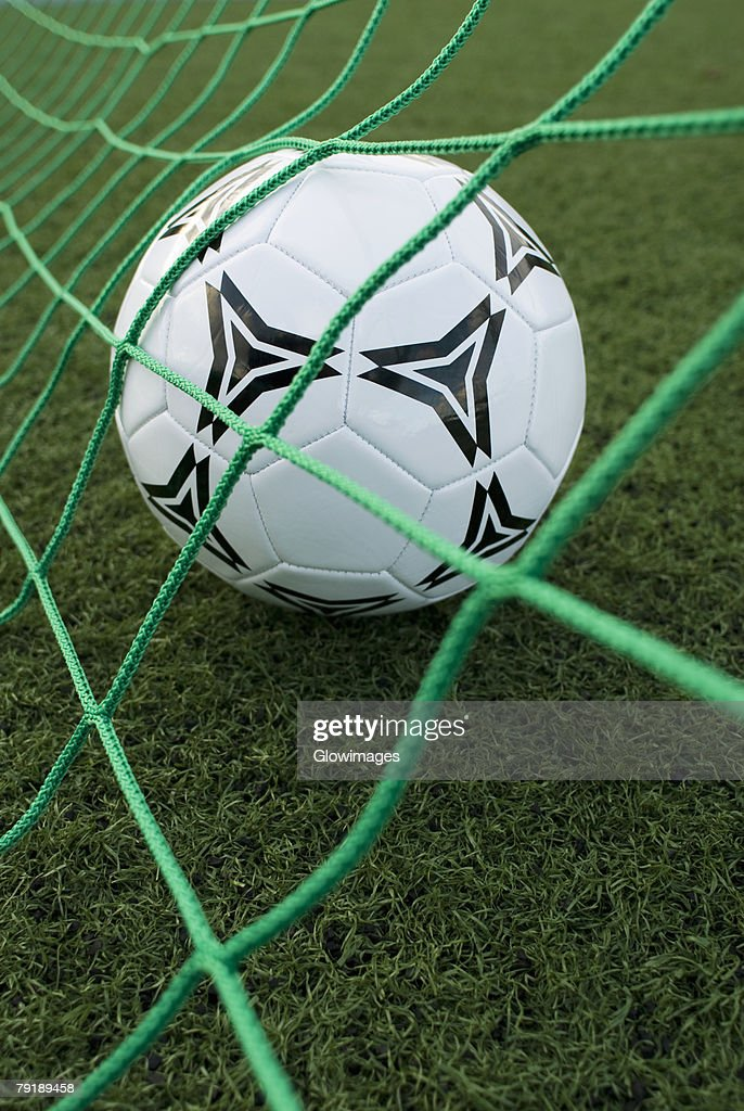 Close-up of a soccer ball in a goal post net : Foto de stock