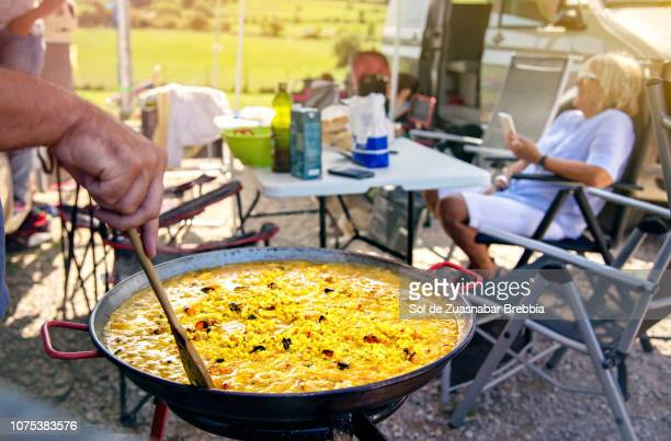 Close-up of a spanish paella in a camping with friends and family on a sunny day