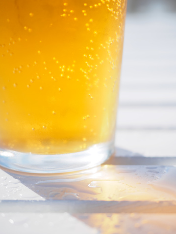 Close-up of a sparkling glass of cider on a wet outdoor table at a bar - gettyimageskorea