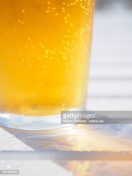 Close-up of a sparkling glass of cider on a wet outdoor table at a bar